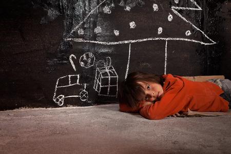 Pobre chico de la calle pensando de regalos de Navidad - tirado en el suelo Foto de archivo