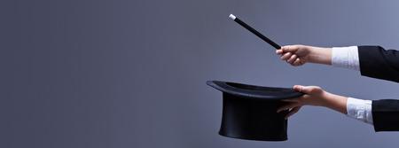alzando la mano: Manos del mago con sombrero y varita m�gica - con copia espacio Foto de archivo