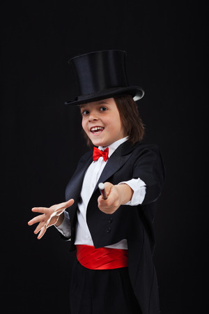 Young magician boy using his magic wand and smiling - on black background
