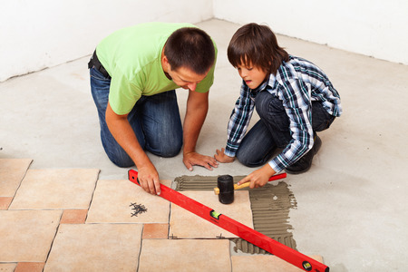 arranging: Man and boy laying ceramic floor tiles together Stock Photo