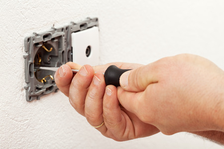 Electrician hand mounting a wall fixture - fastening the screws Stock Photo