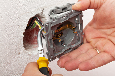 Montage: Elektriker Hand Montage einer Wandhalterung - Montage der Dr�hte mit einer Zange