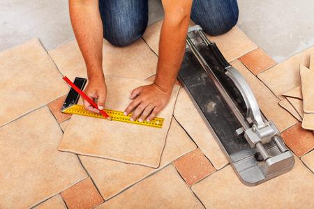 Installazione di pavimenti in ceramica - la misurazione e il taglio dei pezzi, primo piano Archivio Fotografico - 33270592