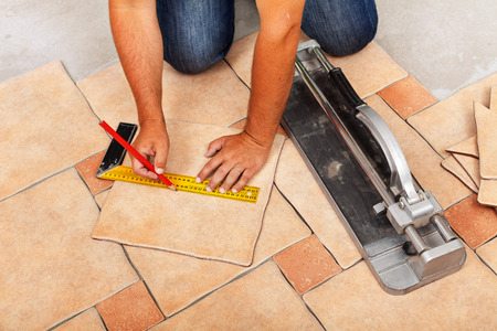 Installing ceramic floor tiles - measuring and cutting the pieces, closeup Zdjęcie Seryjne - 33270592