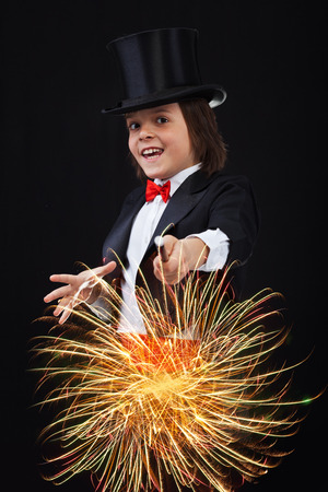 Young magician boy using his magic wand to conjure up sparks and fireworks photo