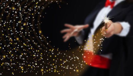 magic show: Magician hands with magic wand conjuring sparkling stars stream - copy space