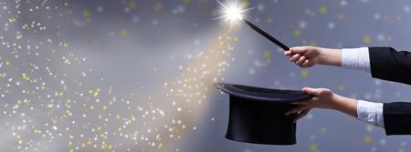 sombrero de mago: Manos del mago con sombrero negro y una varita