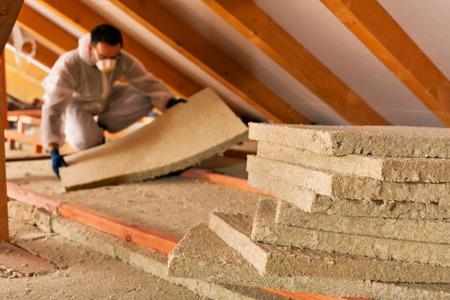 Człowiek instalacji warstwy izolacji termicznej pod dachem - przy użyciu płyt z wełny mineralnej Zdjęcie Seryjne