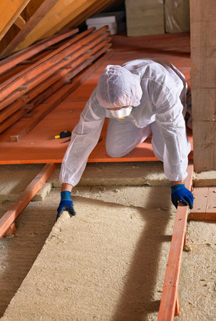 rockwool: Man installing thermal insulation layer under the roof - using mineral wool panels