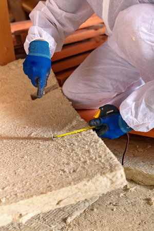 planck: Man installing thermal insulation layer under the roof - using mineral wool panels, closeup Stock Photo