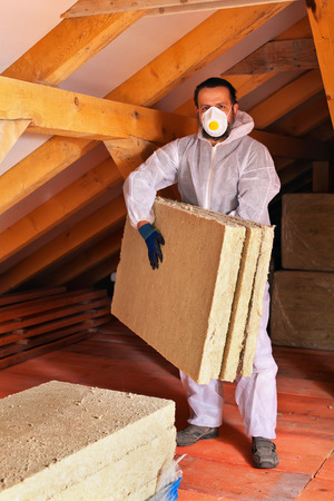 rockwool: Man laying thermal insulation layer under the roof - carry the mineral wool panels