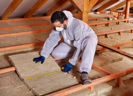 thermal energy: Man laying thermal insulation layer under the roof - measuring a mineral wool panel Stock Photo