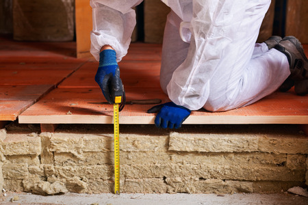 Het meten van de dikte van de thermische isolatie - werknemer handen met meetlint Stockfoto
