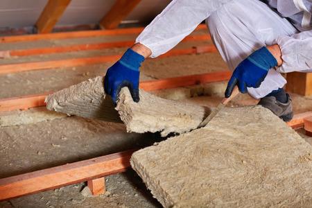 Het installeren van thermische isolatielaag - close-up op handen snijden steenwol