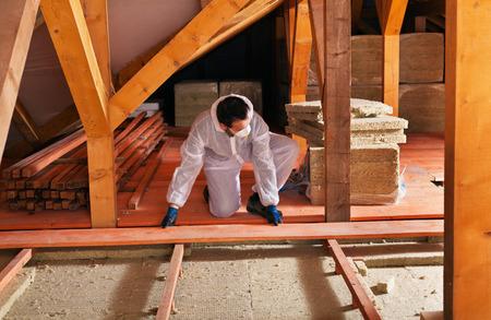 지붕 밑에 단열재를 놓는 남자 - 판자 깔기 설치하기 스톡 콘텐츠