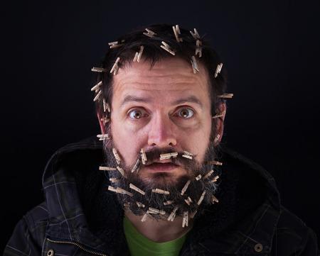 clavados: Apenas lo mantiene unido - hombre barbudo estresante con paños-clavijas con la cabeza Foto de archivo