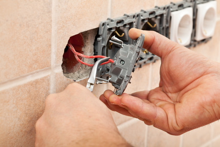 electrician tools: Electrician hands installing wires into a wall fixture using pliers - closeup