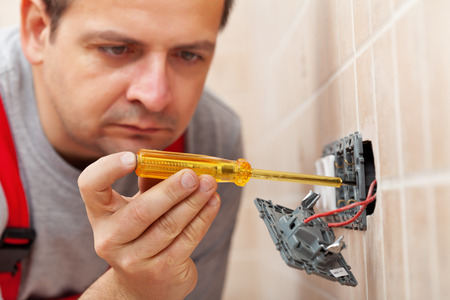 fixture: Electrician checking wall fixture with voltage tester before unmounting it