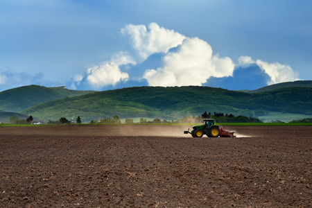 plough machine: Tractor working on the field in late afternoon Stock Photo