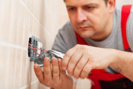 electricista: Electricista arreglando uno de pared eléctrica - la inserción de los cables, de cerca