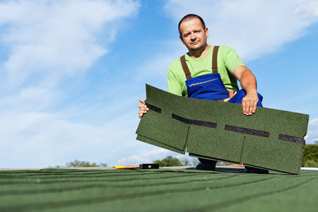 roofing: Man installing bitumen roof shingles - holding a few pieces