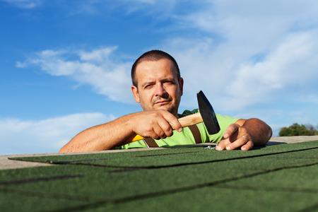 shingles: Hombre de terminar la instalación de las tejas del techo de betún - fijación de las últimas piezas con clavos y martillo