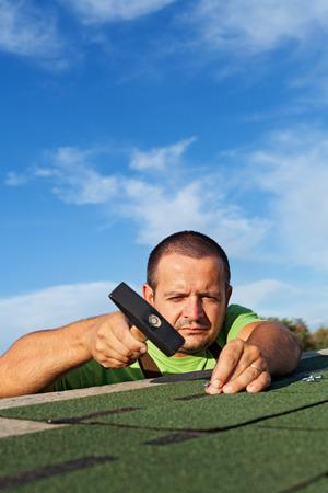 shingles: El hombre la fijaci�n de las tejas del techo de bet�n con clavos y martillo - copia espacio