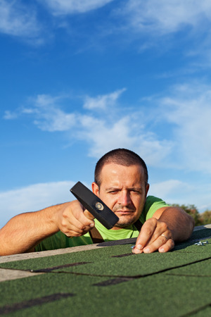 shingles: Man fastening bitumen roof shingles with nails and hammer - copy space Stock Photo