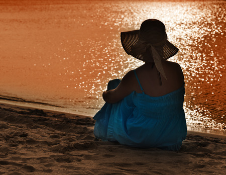 Woman watching the light playing on the sea - silhouette photo