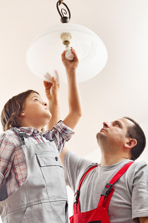 light worker: Father and son changing lightbulb in a ceiling lamp together