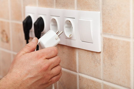 Hand plugging power cord into a wall outlet - closeup