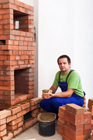 fireclay: Man building a masonry heater - applying clay mortar to a brick Stock Photo
