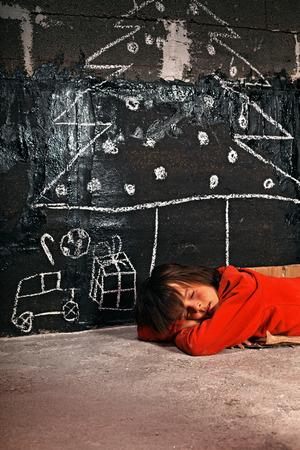 pobre: Pobre chico durmiendo en la calle soñando con los regalos de Navidad Foto de archivo