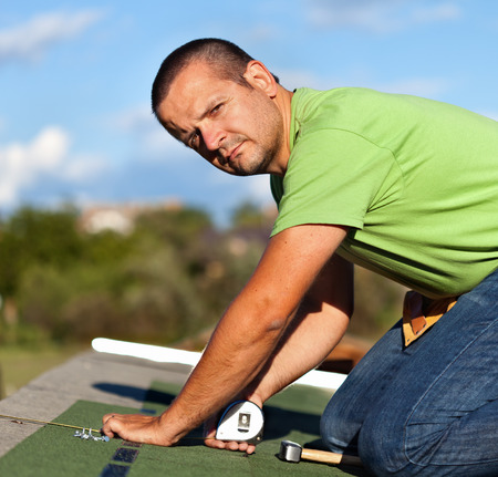 shingles: Man installing bitumen roof shingles - taking measurmenets for the last row