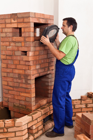 firebox: Worker building a traditional masonry heater - fitting an iron and glass door into place
