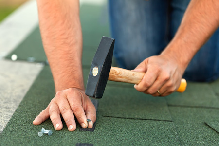 roofs: Worker hands installing bitumen roof shingles - fastening one with nails, closeup Stock Photo