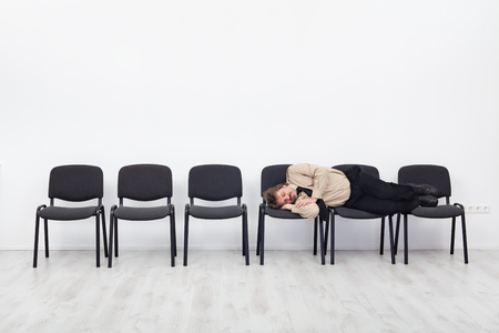 tired person: Office worker asleep on row of chairs - coping with overtime
