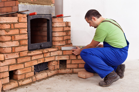 firebox: Construction worker building a traditional masonry heater - checking it with a spirit level