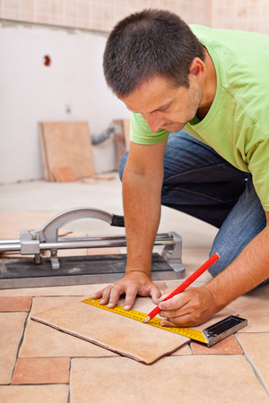 tile cutter: Worker installs ceramic tiles - marking them for cutting Stock Photo