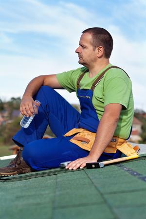 taking a break: Worker installing bitumen shingles - taking a break sitting on the roof Stock Photo