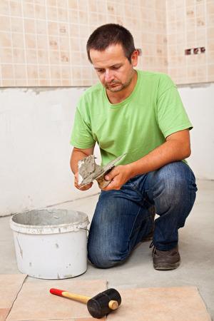 tile adhesive: Man installs ceramic floor tiles - preparing to apply the adhesive Stock Photo