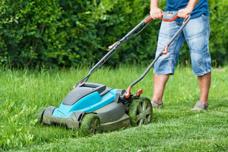 mow: Man mowing the lawn with blue lawnmower in summertime - closeup Stock Photo