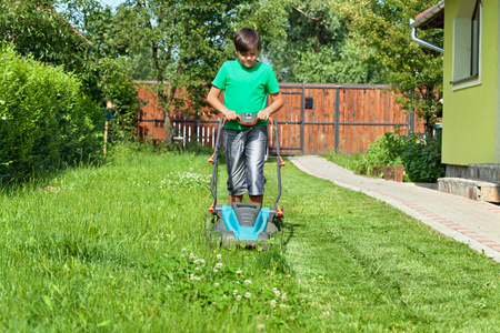 Boy cutting grass around the house in summertime - focusing on the operation Stockfoto