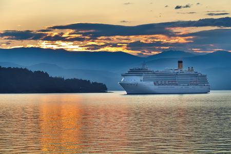 archipelago: Sunrise in the greek archipelago with cruise ship approaching land Stock Photo