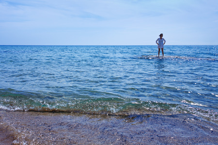 Woman standing in the shallow waters of the sea near the shore - strong backlight photo