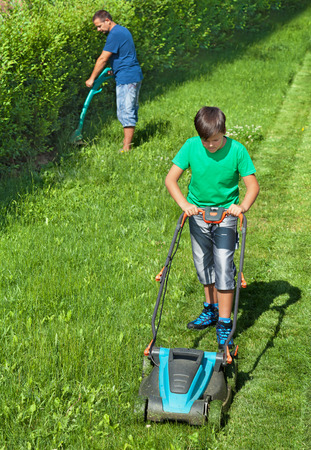 father and son: Boy mowing the lawn and man trimming the edges - summer activities