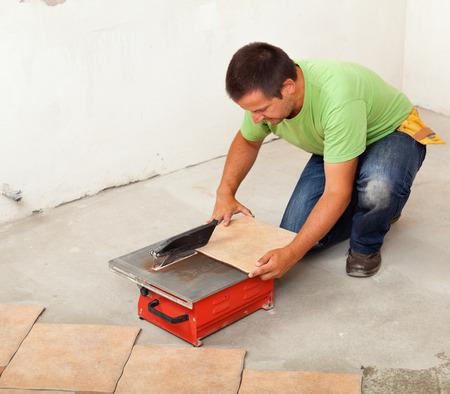 tile cutter: Man cutting ceramic floor tile - knealing by a cutter machine