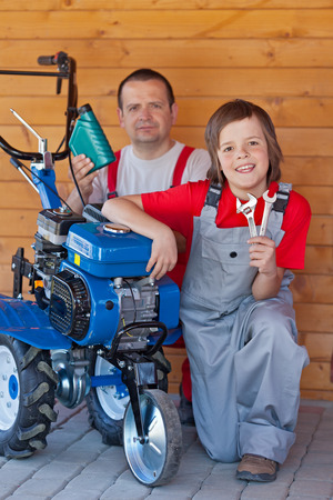 servicing: Man and young boy servicing tiller machine - preparing for spring operations