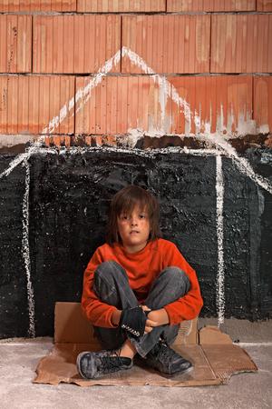 vagabundos: niño sin hogar joven que se sienta en la calle - hacer una casa imaginaria Foto de archivo