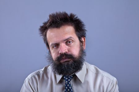Exhausted man with bushy hair and beard on gray background - copy space Stock Photo